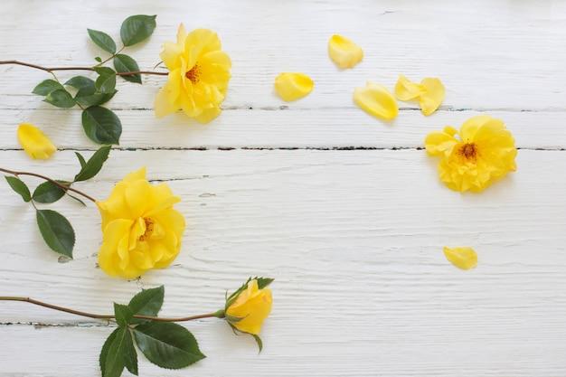 Gelbe rosen auf weißem hölzernem hintergrund