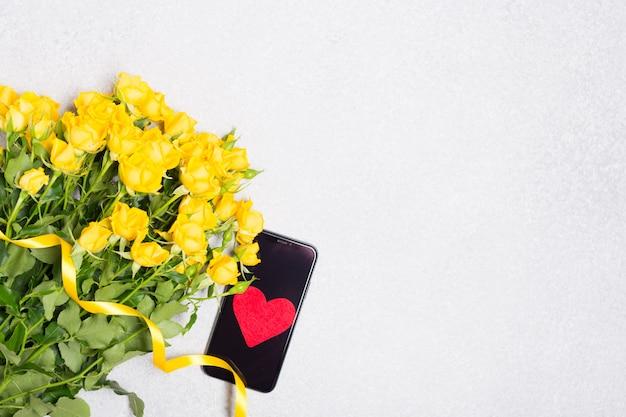 Gelbe rosenblumen und telefon mit rotem herzen auf weißem tischhintergrund