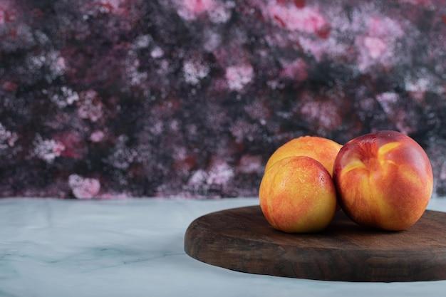 Gelbe rote pfirsiche auf holzbrett.
