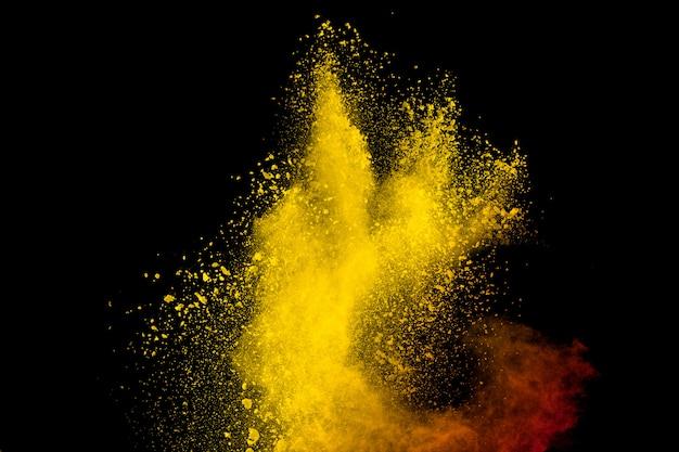 Gelbe rote pulverexplosionswolke auf schwarzem hintergrund.