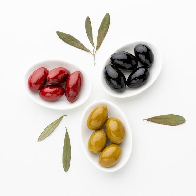 Gelbe rote schwarze oliven auf platten mit blättern