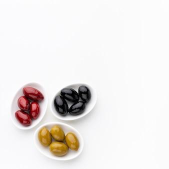 Gelbe rote schwarze oliven auf tellern