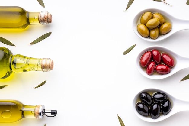 Gelbe rote schwarze oliven in den löffeln mit blättern und ölflaschen