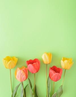 Gelbe, rote und bunte tulpenblume auf einem grünen hintergrund, der unten auf dem foto angeordnet ist. natur-stillleben flach legen konzept.