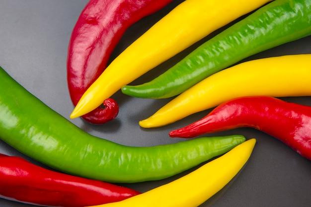 Gelbe, rote und grüne scharfe chili auf einem teller. pfeffer. pflanzliche vitaminnahrung.
