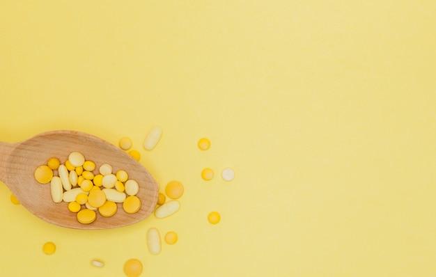 Gelbe runde vitaminpillen im löffel auf einem gelben