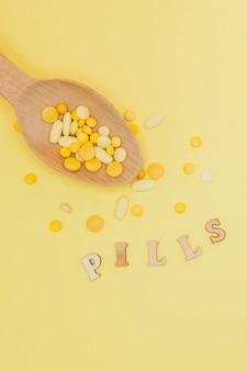 Gelbe runde vitaminpillen im löffel auf einer gelben wand, kopierraum