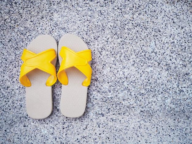 Gelbe sandale am rand des schwimmbades.