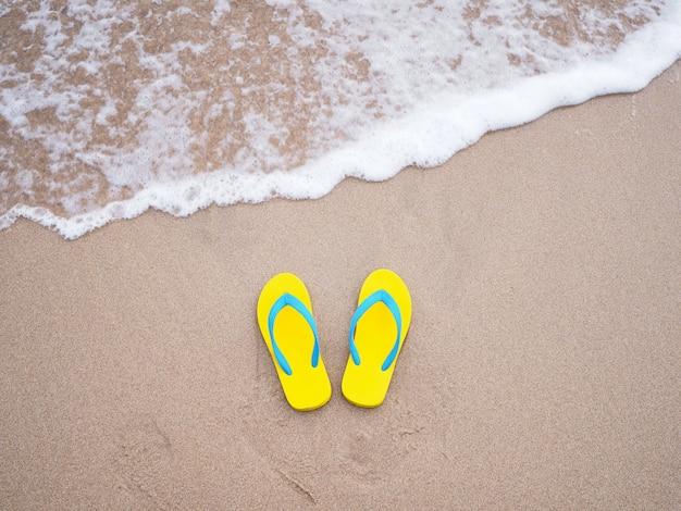 Gelbe sandale auf sommerstrand des beige sandes