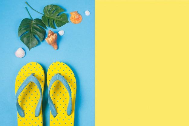 Gelbe sandalen auf blauem und gelbem farbhintergrund