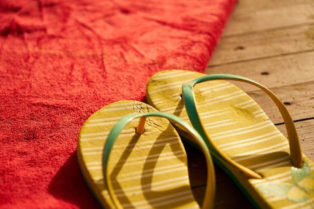 Gelbe sandalen auf einem roten handtuch