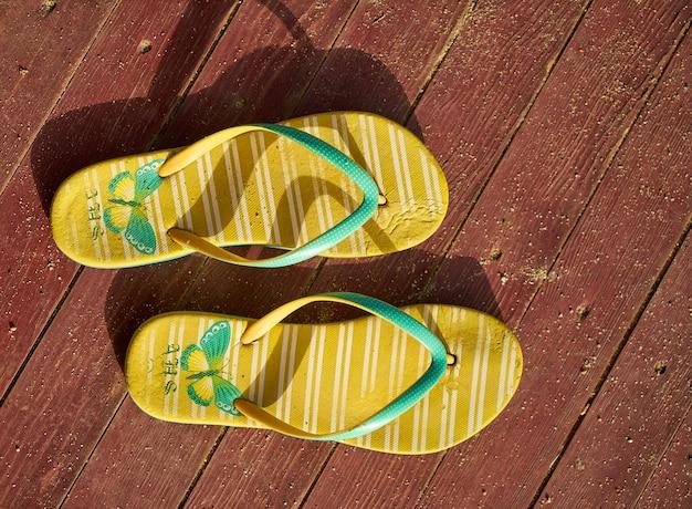 Gelbe sandalen auf holz
