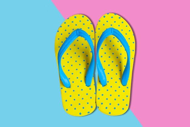 Gelbe sandalen auf rosa und blauem farbhintergrund, flach legen foto