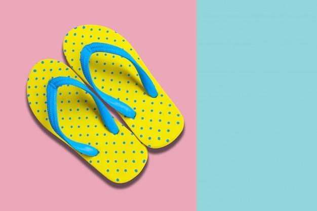 Gelbe sandalen auf rosa und blauem farbhintergrund
