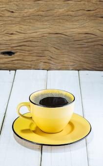 Gelbe schale heißes holz des kaffees auf dem tisch weißes