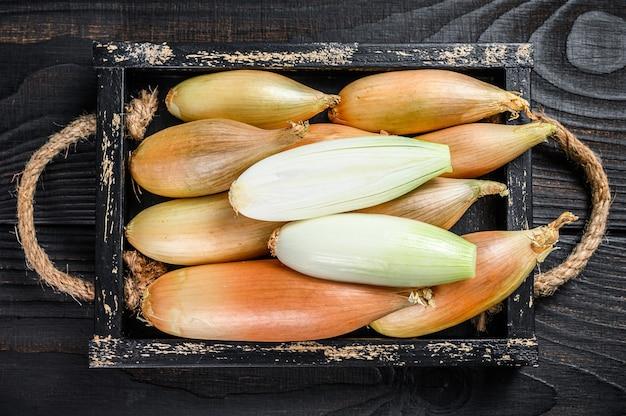 Gelbe schalottenzwiebeln, in zwei hälften geschnitten in einer holzkiste