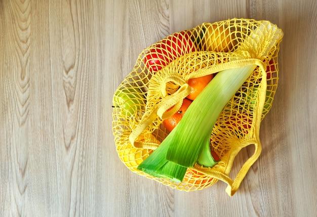 Gelbe schnur-einkaufstasche mit gemüse und früchten, die auf dem küchentisch hängen