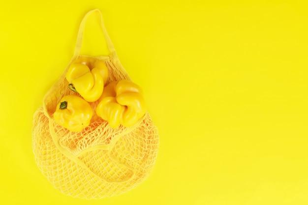 Gelbe schnur-tasche mit gelben frischen pfeffern. öko-bio-produkte, hässliche natürliche lebensmittel, gesunde, diätetische und vegetarische lebensmittel