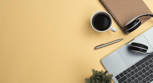 Gelbe schreibtischtabelle des büroarbeitsplatzes mit laptop, kaffee, mobile, notizbuch, anlage. flach liegen