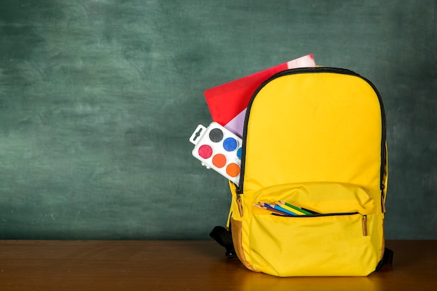 Gelbe schultasche mit stiften und farben