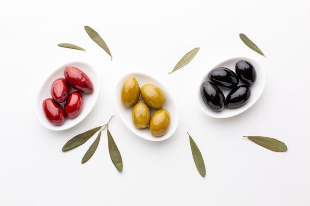 Gelbe schwarze rote oliven auf platten mit blättern