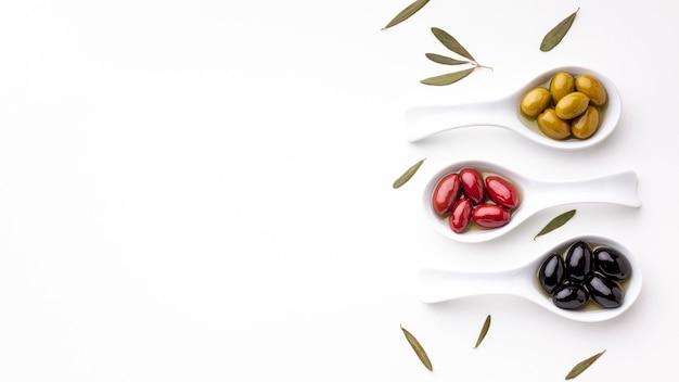 Gelbe schwarze rote oliven in den löffeln mit blättern und kopienraum
