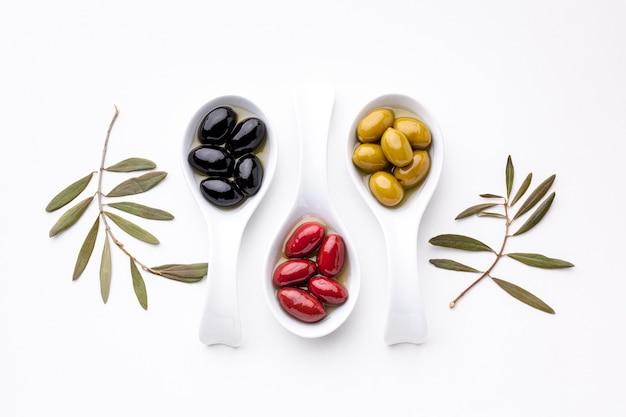 Gelbe schwarze rote oliven in den löffeln mit blättern