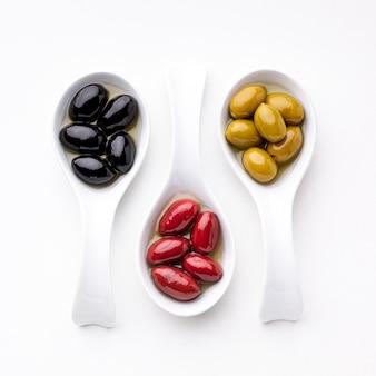 Gelbe schwarze rote oliven in den löffeln