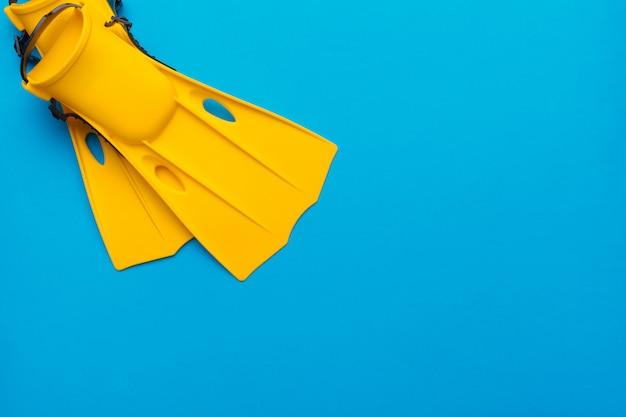 Gelbe schwimmende flossen auf farbigem hintergrund