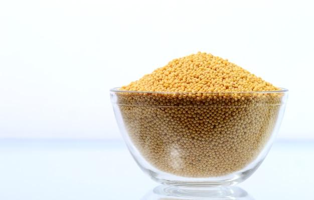 Gelbe senfkörner in der glasschale lokalisiert auf weißem hintergrund