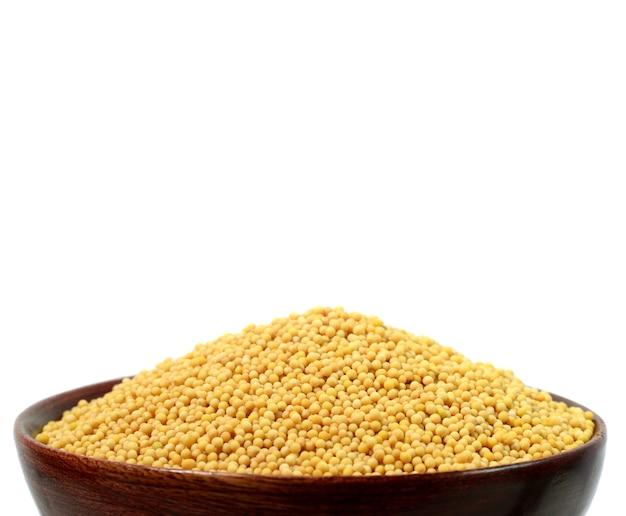 Gelbe senfkörner in der holzschale isoliert