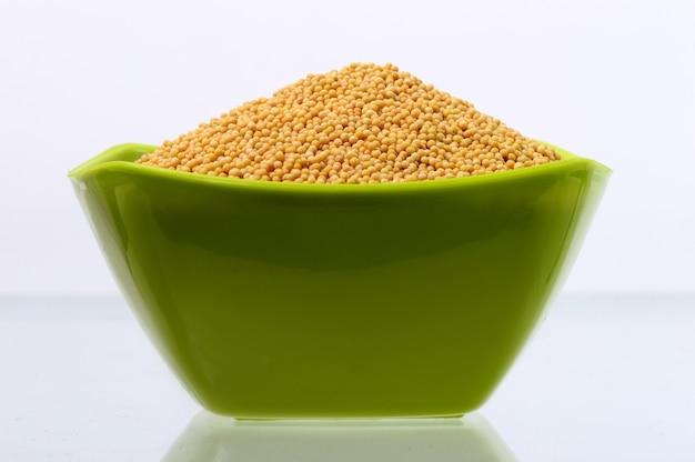 Gelbe senfkörner in grüner schüssel isoliert