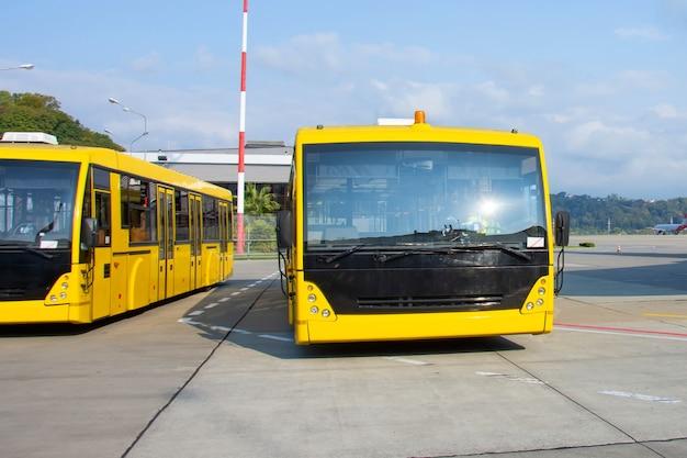 Gelbe shuttle-busse transportieren passagiere vom terminalgebäude zum flugzeug.