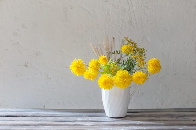 Gelbe sommerblumen im krug auf weißer oberfläche
