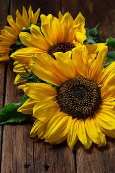 Gelbe sonnenblume auf hölzernem hintergrund