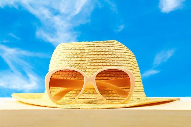 Gelbe sonnenbrille und hut auf hölzernem regal auf blauem himmel