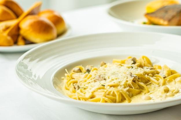 Gelbe spaghetti carbonara mit weißer sahnesauce im teller auf tisch - italienischer essensstil