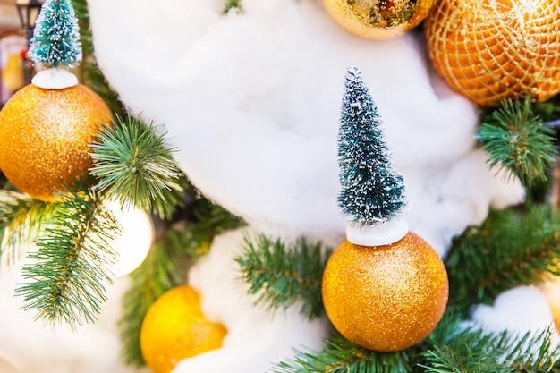 Gelbe spielwaren des neuen jahres auf schneebedecktem weihnachtsbaum