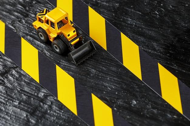Gelbe spielzeugplanierraupe. schwarzes und gelbes zaunband