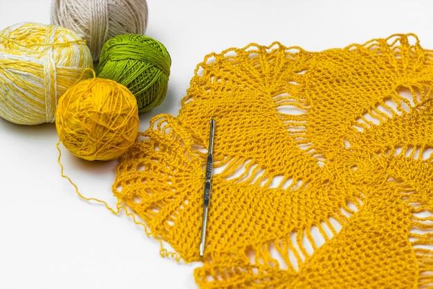 Gelbe spitzenhäkelarbeit, garnknäuel und häkelnadel
