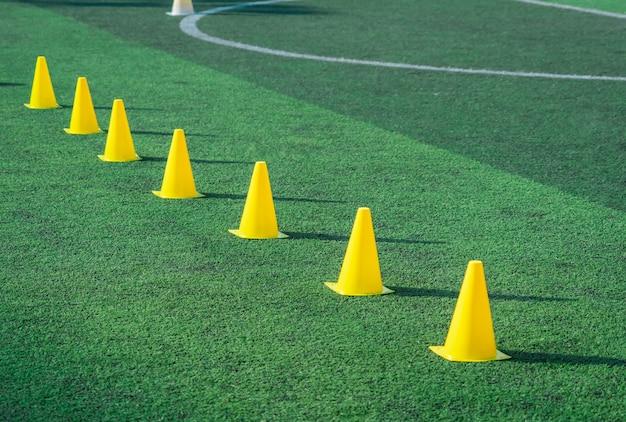 Gelbe sporttrainingskegel auf fußballplatz