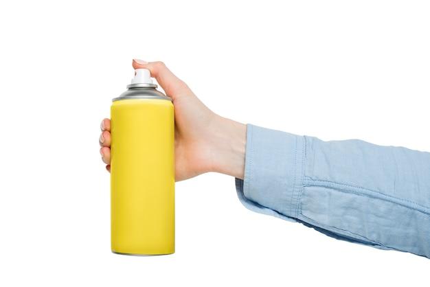 Gelbe sprühdose zum sprühen in eine weibliche hand. keine inschriften. weißer hintergrund