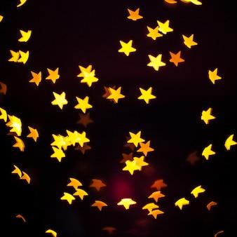 Gelbe Sterne der Nahaufnahme auf Dunkelheit