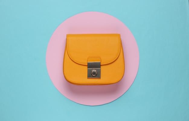 Gelbe stilvolle ledertasche auf blauem hintergrund mit rosa pastellkreis. draufsicht. minimalistisches mode-stillleben