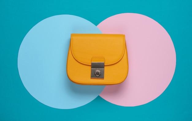 Gelbe stilvolle ledertasche auf hintergrund mit blau-rosa pastellkreisen. draufsicht. minimalistisches mode-stillleben