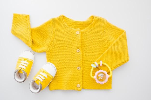 Gelbe strickjacke der draufsicht mit schuhen