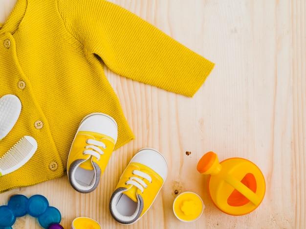 Gelbe strickjacke der draufsicht mit spielwaren