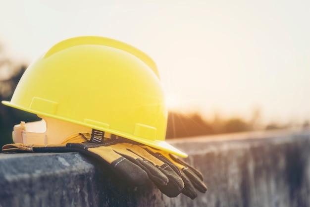 Gelbe sturzhelme und handschuhe auf dem zementboden mit dem hintergrundlicht und -sonnenuntergang.