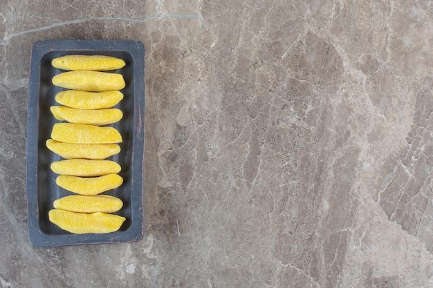 Gelbe süße bonbons in folge auf holzbrett.