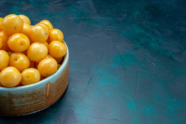 Gelbe süße kirschen reif weich auf dunkelblauen schreibtischfrucht süße fres milder sommer
